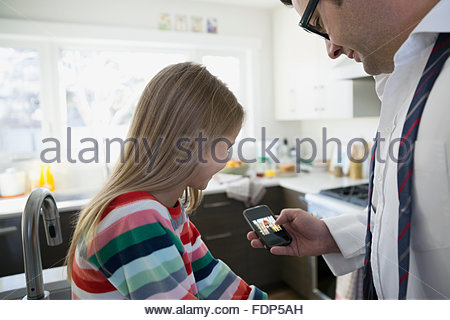 Father and daughter using cell phone in kitchen - Stock Photo