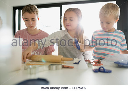 Brothers and sister baking cookies - Stock Photo