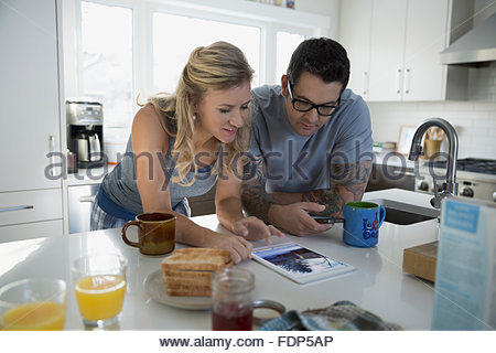 Couple drinking coffee using digital tablet kitchen - Stock Photo