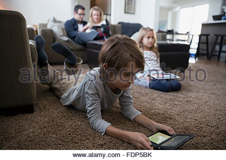 Boy playing video game on living room floor - Stock Photo