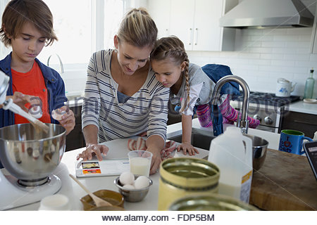 Mother and children baking with digital tablet kitchen - Stock Photo
