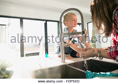 mother washing hands in kitchen sink - Stock Photo