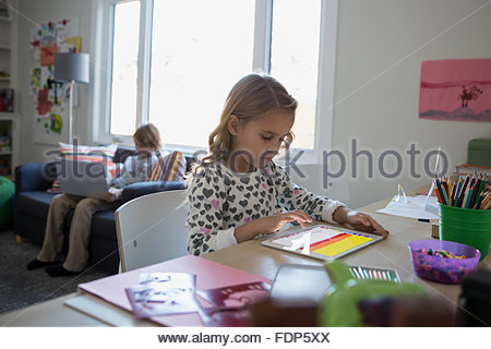 Girl using digital tablet at desk - Stock Photo