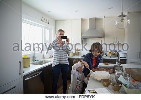 Mother photographing children icing cake in kitchen - Stock Photo
