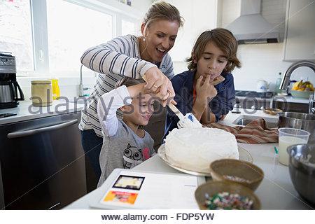 Family baking cake in kitchen - Stock Photo