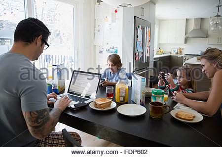 Family using cell phones and laptop breakfast table - Stock Photo