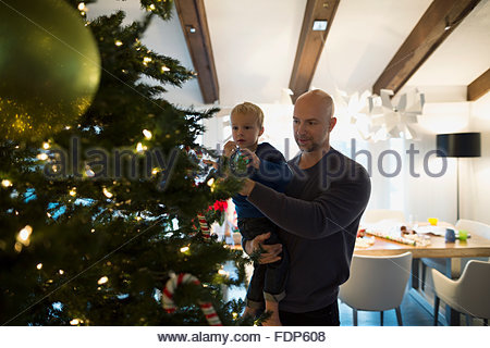 Father and son decorating Christmas tree - Stock Photo