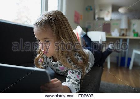 Girl using digital tablet on living room sofa - Stock Photo