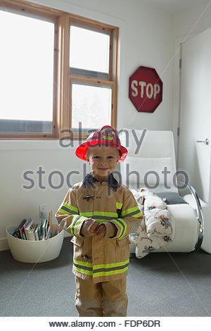 Portrait cute boy in fireman costume - Stock Photo