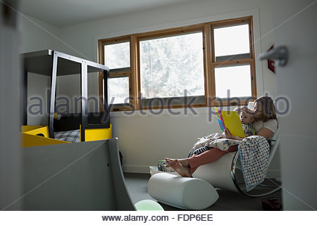 Mother and son reading book in bedroom - Stock Photo