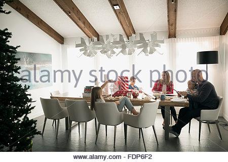 Family eating at dining table near Christmas tree - Stock Photo