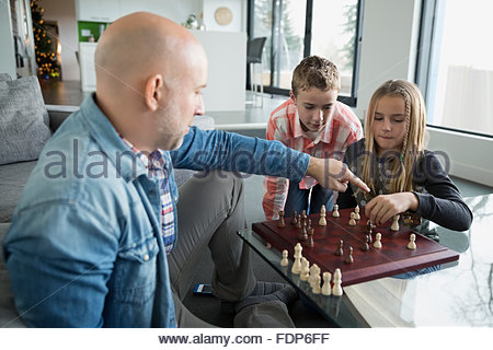 Father and children playing chess - Stock Photo