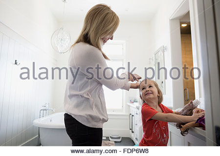 mother brushing daughters hair bathroom - Stock Photo