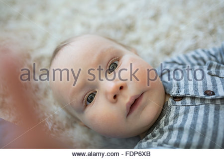Portrait cute baby boy laying on rug - Stock Photo