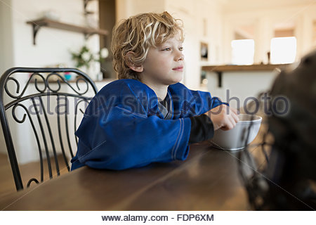 Pensive boy eating cereal at table - Stock Photo
