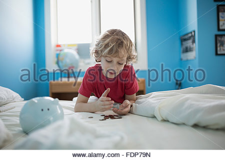 Boy counting piggy bank coins on bed - Stock Photo