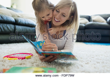 Daughter laying top mother reading book rug - Stock Photo