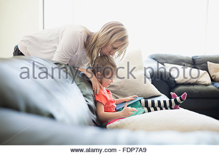 Mother watching daughter read book living room sofa - Stock Photo