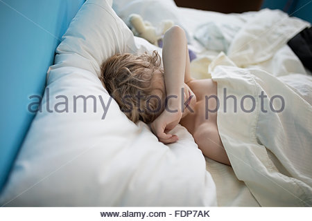Tired boy sleeping with arm over eyes - Stock Photo