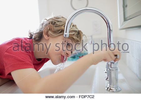 Boy drinking water from bathroom faucet - Stock Photo