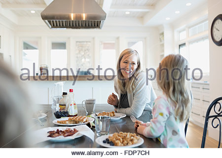 Mother and daughter eating waffles at breakfast table - Stock Photo
