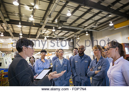 Manager with digital tablet leading meeting in factory - Stock Photo
