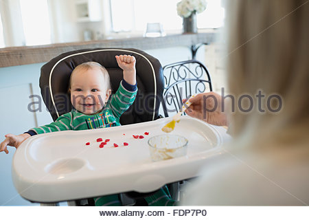 Mother feeding enthusiastic baby boy in high chair - Stock Photo