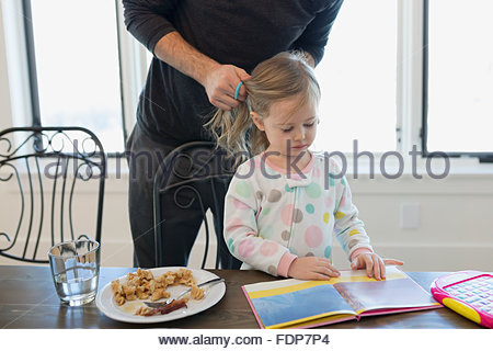 father fixing daughters hair reading - Stock Photo