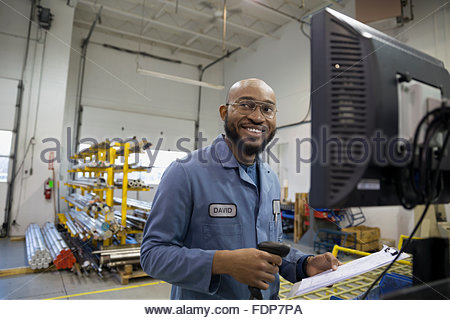 Smiling worker with clipboard at computer in factory - Stock Photo