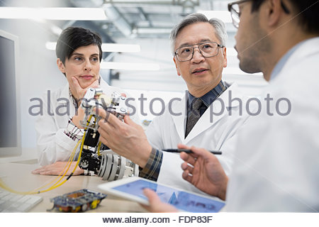 Engineers discussing and assembling robotics in factory - Stock Photo