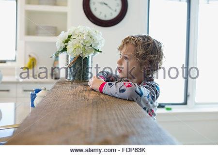 Boy in pajamas leaning on kitchen breakfast bar - Stock Photo