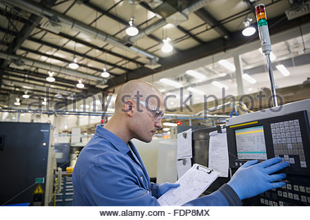 Worker with clipboard at control panel in factory - Stock Photo
