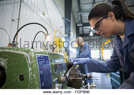 Worker using machinery in textile factory - Stock Photo
