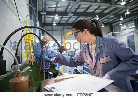 Engineer with clipboard at machinery in textile factory - Stock Photo