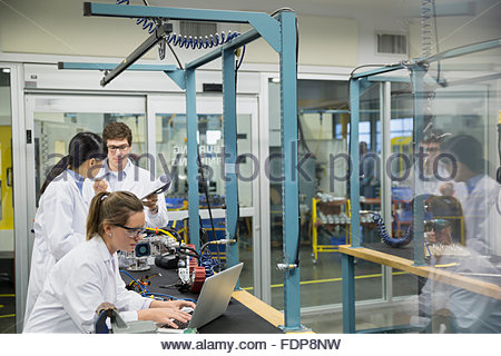 Engineers at laptop assembling robotics in factory - Stock Photo
