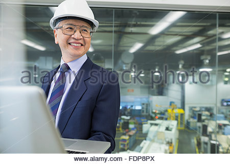 Smiling manager using laptop in factory - Stock Photo