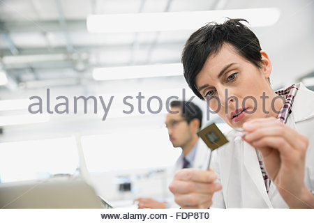 Focused engineer examining microchip - Stock Photo
