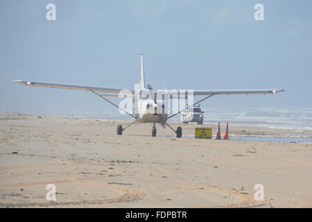 Light plane taking off from the beach at Fraser Island, Queensland - Stock Photo