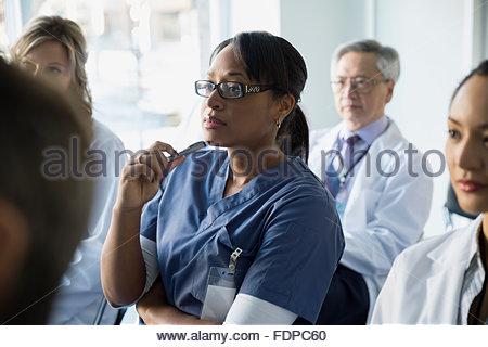 Attentive nurse listening in seminar audience - Stock Photo