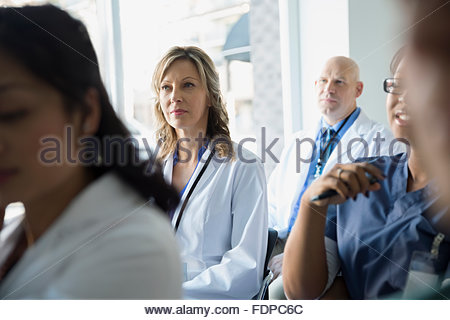 Attentive doctors listening in seminar audience - Stock Photo