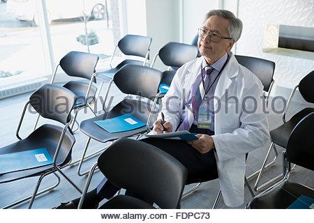 Doctor taking notes in seminar - Stock Photo