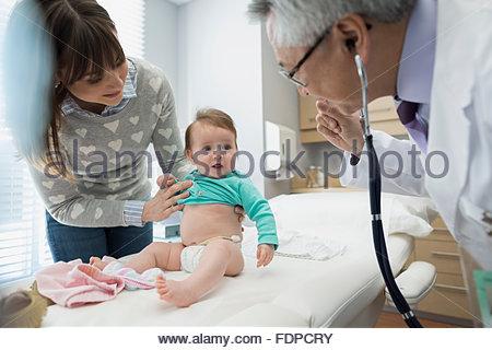 Pediatrician examining baby in examination room - Stock Photo
