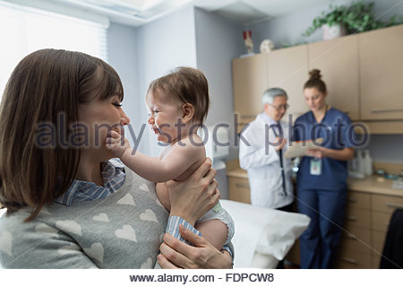 Mother holding baby in pediatrician examination room - Stock Photo