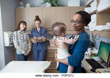 Pediatrician holding baby in examination room - Stock Photo