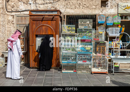 A Local Woman Withdraws Money From A Cashpoint Machine, Souk Waqif, Doha, Qatar - Stock Photo