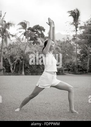 A woman doing Warrior One pose (Virabhadrasana One) outdoors at The Farm at San Benito, Philippines. - Stock Photo