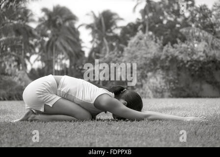 A woman doing a yoga pose outdoors at The Farm at San Benito, Philippines. - Stock Photo