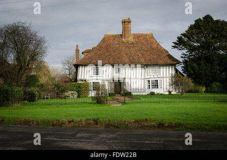 An ancient white half-timbered cottage on a village green in Kent, UK - Stock Photo