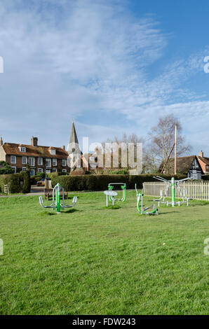 Exercise equipment on Woodchurch village green, Kent, UK, with All Saints church and brick and tiled cottages in - Stock Photo