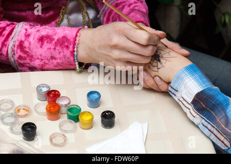 woman draws a spider on girl hand - Stock Photo
